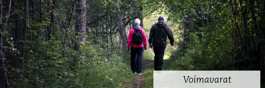 kurssin teemana voimavarat, kaksi henkilöä kävelee metsässä ulkoiluvarusteissa